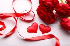 两朵心脏、丝带和玫瑰在桌上 免版税图库摄影