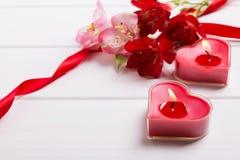 两朵心脏形状蜡烛和花 库存照片