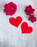 两朵红色心脏和猩红色玫瑰在白板,顶视图 免版税库存图片