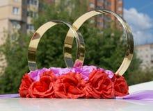 两朵金黄圆环和花在婚礼汽车 免版税库存图片