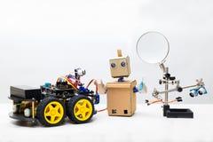 两机器人和部分装配的一个机器人在一白色backgroun 免版税库存照片