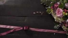 两条丝绸桃红色丝带蔓延黑暗的木表面,花美丽的花束上在框架的 慢的行动 股票录像