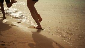 两条孩子腿运行在海滩的,慢动作 股票录像