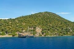 两条小船在有古老废墟的绿色海岛停泊了 库存图片