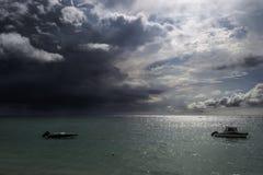 两条小船海上停泊了在剧烈的云彩下在日落 免版税库存照片