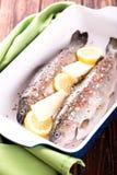 两条新鲜的鳟鱼用柠檬和黄油在平底锅 免版税库存图片