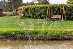 两条木摇摆长凳在有水下落的庭院里在前景 库存照片