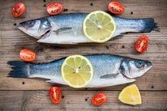 两条未加工的雪鱼鱼用柠檬和西红柿在木背景 免版税库存照片