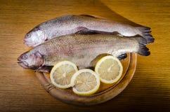 两条未加工的鳟鱼鱼用在木板材的柠檬 免版税图库摄影