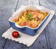 两条烤鸡腿用土豆和新鲜的绿色香料在盘子 库存图片