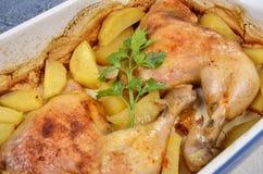 两条烤鸡腿用土豆和新鲜的绿色香料在盘子 库存照片