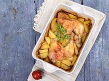 两条烤鸡腿用土豆和新鲜的绿色香料在盘子 图库摄影