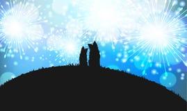 两条狗剪影坐小山的上面与蓝色烟花的在背景 免版税库存照片
