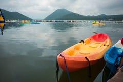 两条独木舟小船在湖水漂浮有天空,山是bac 免版税图库摄影