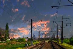 两条线铁路在国家在日落天空背景支持 在铁路的电杆 免版税库存照片