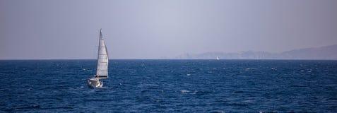 两条风船种族在风帮助下,在风平浪静 蓝天和山背景,横幅 免版税库存照片