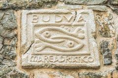 两条鱼-市的标志布德瓦,黑山 布德瓦的历史标志在一座古老城堡的墙壁上的 免版税图库摄影
