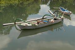 两条巴厘语全国木小船在死水,水表面反射与白色云彩和绿色植被, Ba的蓝天 免版税库存照片