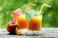 两杯与一支红色和绿色伞和管的桃子汁 图库摄影