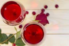 两杯与一朵红色玫瑰的红葡萄酒 库存图片