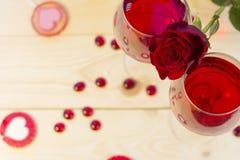 两杯与一朵红色玫瑰的红葡萄酒 库存照片