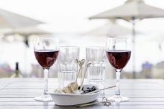 两杯与一顿快餐的红葡萄酒在海滩 库存图片