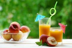 两杯与伞的桃子汁在一张木桌上 图库摄影
