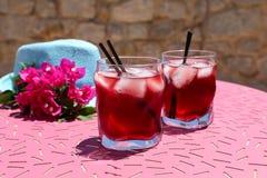 两杯与冰的夏天红色鸡尾酒在一个蓝色帽子旁边和九重葛花小树枝在一张桃红色桌上的 免版税库存图片