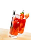 两杯与冰的草莓鸡尾酒在轻的木桌上 免版税库存照片