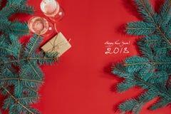 两杯与圣诞树分支和小礼物的香槟在红色背景 库存图片