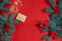两杯与圣诞树分支和小礼物的香槟在红色背景 库存照片