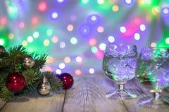 两杯与圣诞树的圣诞节香槟装饰红色和银球反对轻的bokeh背景 免版税库存照片