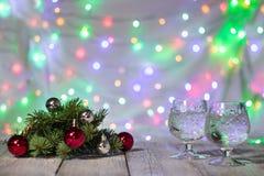 两杯与圣诞树的圣诞节香槟装饰红色和银球反对轻的bokeh背景 库存图片