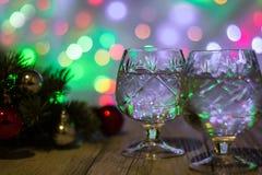 两杯与圣诞树的圣诞节香槟装饰红色和银球反对轻的bokeh背景 免版税库存图片