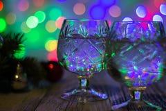 两杯与圣诞树的圣诞节香槟装饰红色和银球反对轻的bokeh背景 免版税图库摄影