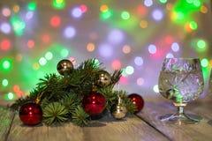 两杯与圣诞树的圣诞节香槟装饰红色和银球反对轻的bokeh背景 库存照片