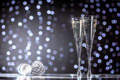 两杯与圣诞节玩具的香槟 欢乐光bok 免版税图库摄影
