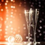 两杯与圣诞节玩具的香槟 欢乐光bok 免版税库存照片