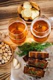 两杯低度黄啤酒、开心果和油煎方型小面包片在木t 免版税库存照片