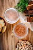 两杯低度黄啤酒和快餐、开心果和油煎方型小面包片 免版税库存图片