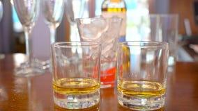 两杯兰姆酒,威士忌酒酒精 男服务员一个完善的鸡尾酒的措施数量 概念:饮料,迪斯科,乐趣,朋友 影视素材