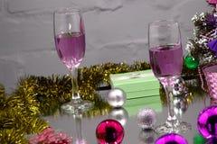 两杯冷的香槟和圣诞节装饰在光和砖墙背景  紫色 库存图片