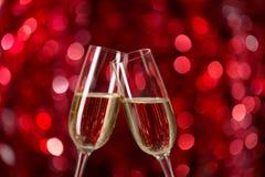 两杯反对红色背景的香槟与闪闪发光 非常浅景深 选择聚焦 免版税库存图片