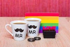 两杯咖啡、快乐旗子和一个黑礼物盒有婚姻的敲响 免版税库存照片