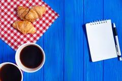 两杯咖啡、新月形面包和开放笔记薄与笔在蓝色 免版税库存照片