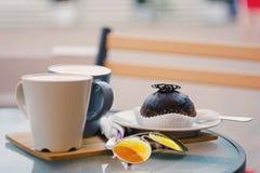 两杯咖啡和一个巧克力蛋糕在桌上 免版税库存照片