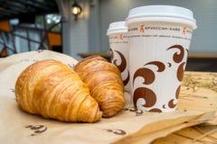 两杯咖啡和两个新月形面包在街道上在新月形面包 库存照片