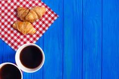 两杯咖啡和新月形面包在蓝色木桌上 免版税库存照片
