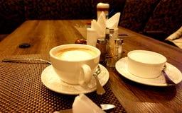 两杯咖啡和装置,站立在桌上在餐馆:盐瓶、胡椒振动器和立场餐巾的 库存照片