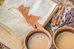 两杯咖啡在一本开放书附近的 图库摄影